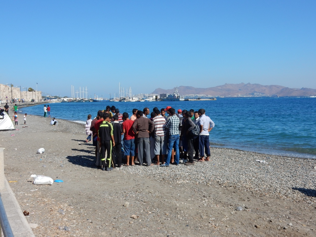 Sevastianos returning registration papers to men waiting to leave the island. Kos Harbour.